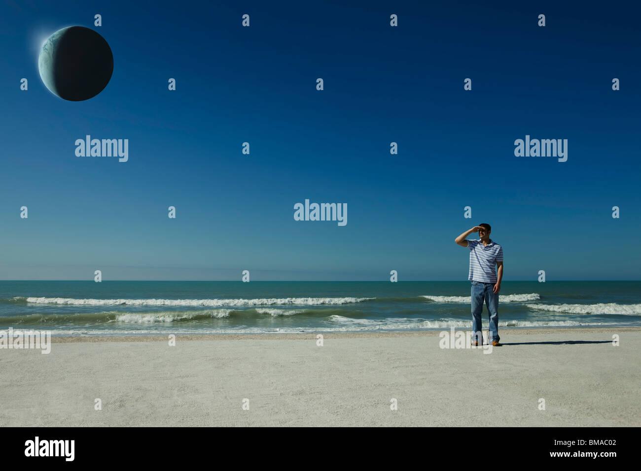 Mann am Strand beobachten eclipse Stockbild