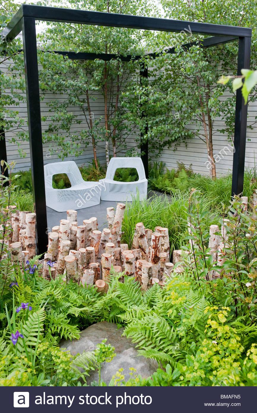 Natürlich modisch Garten von NDG + entworfen. Sitzecke mit Metallgitter Sitze, schwarze Pergola, Birkenholz Stockbild