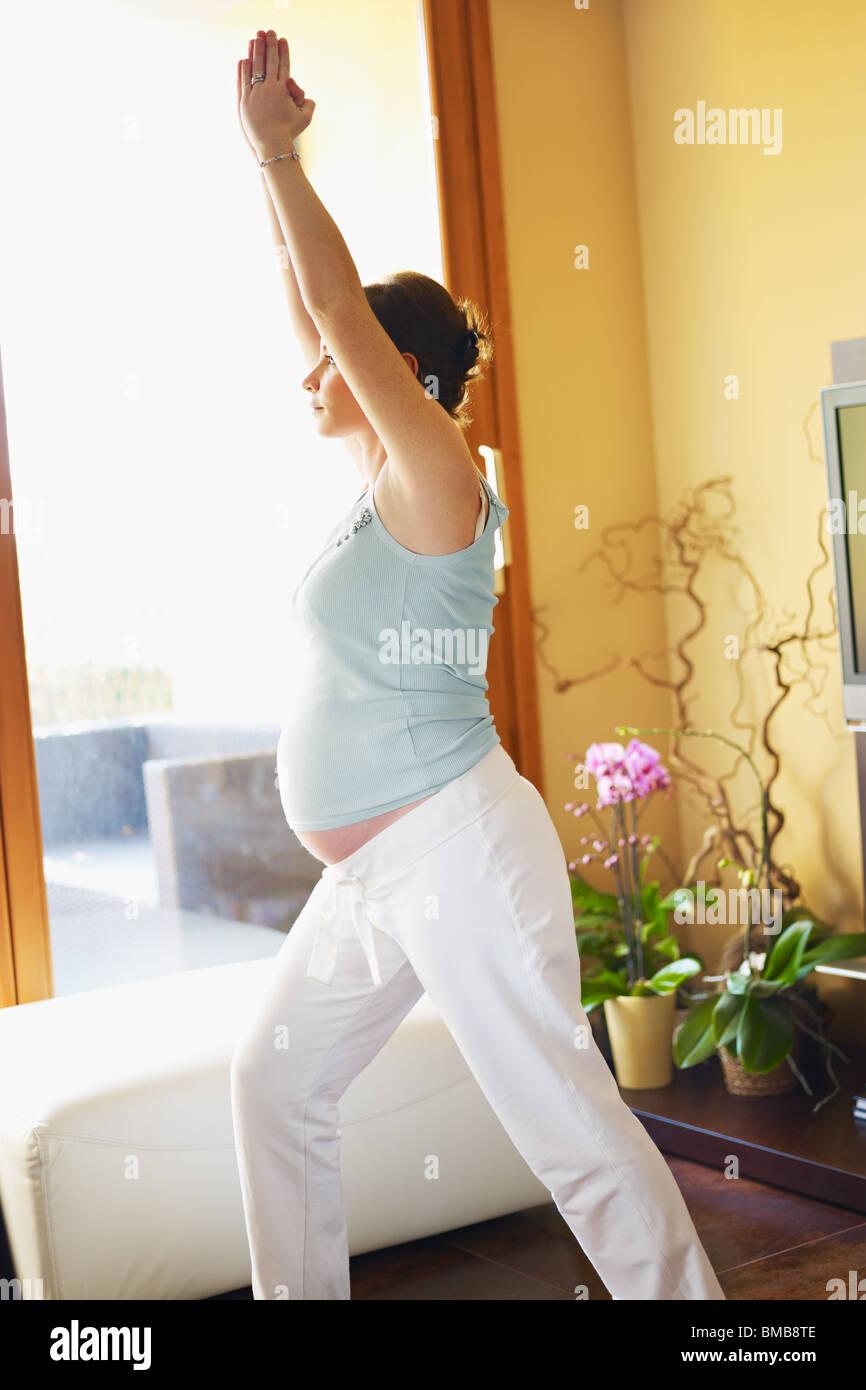 italienische 6 Monate schwangere Frau mit ausgestreckten Armen tun Yoga-Übung zu Hause. Vertikale Form, Textfreiraum Stockbild