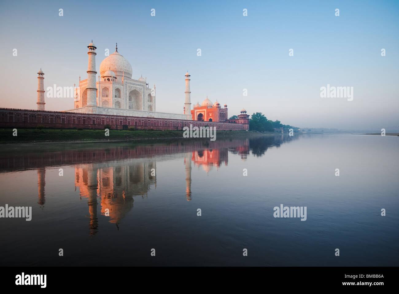 Das Taj Mahal leuchtet rot bei Tagesanbruch neben dem heiligen Fluss Jamuna. Stockbild