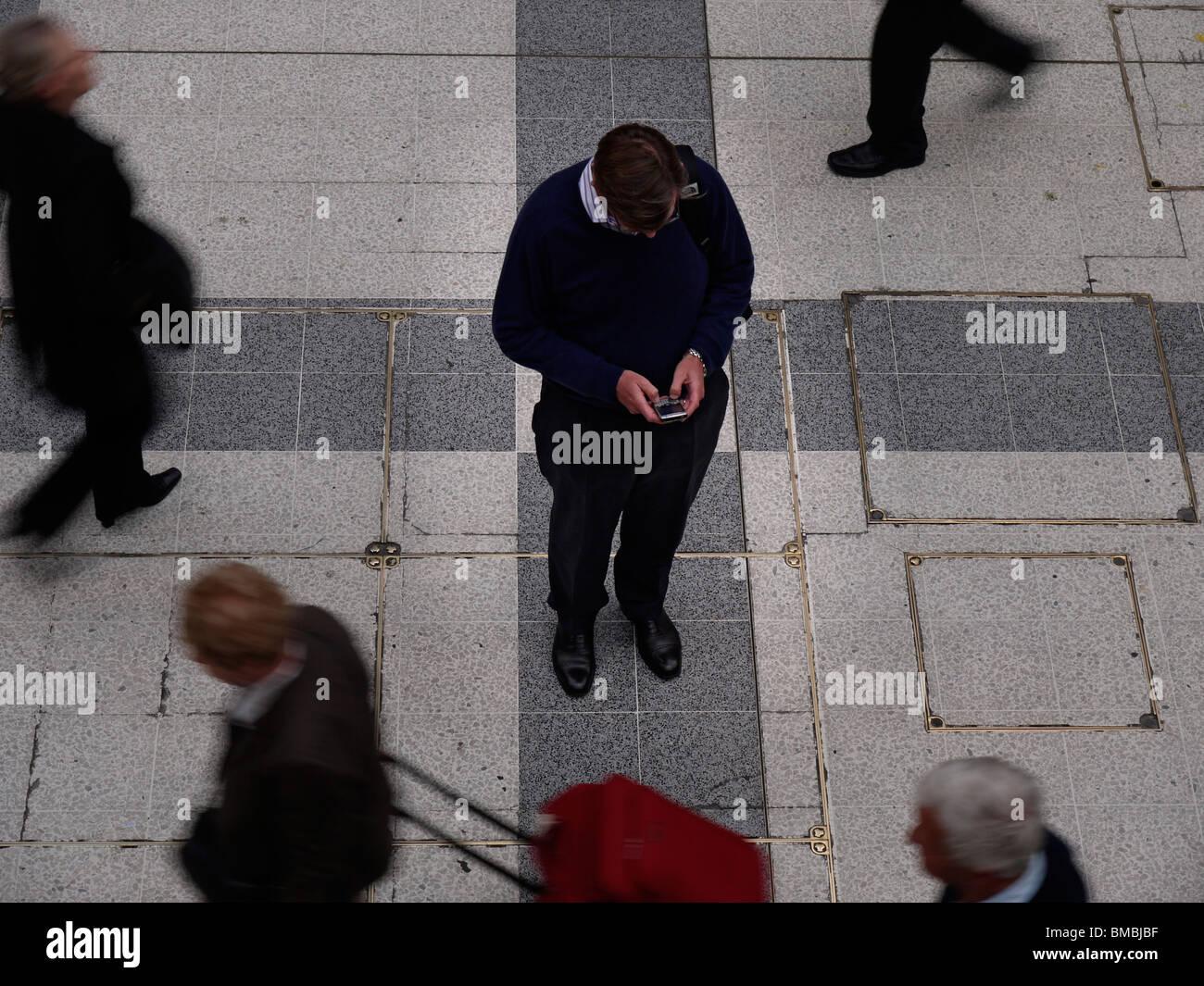 Mann, die SMS auf dem Handy unter Reisenden während der Rush hour Stockbild
