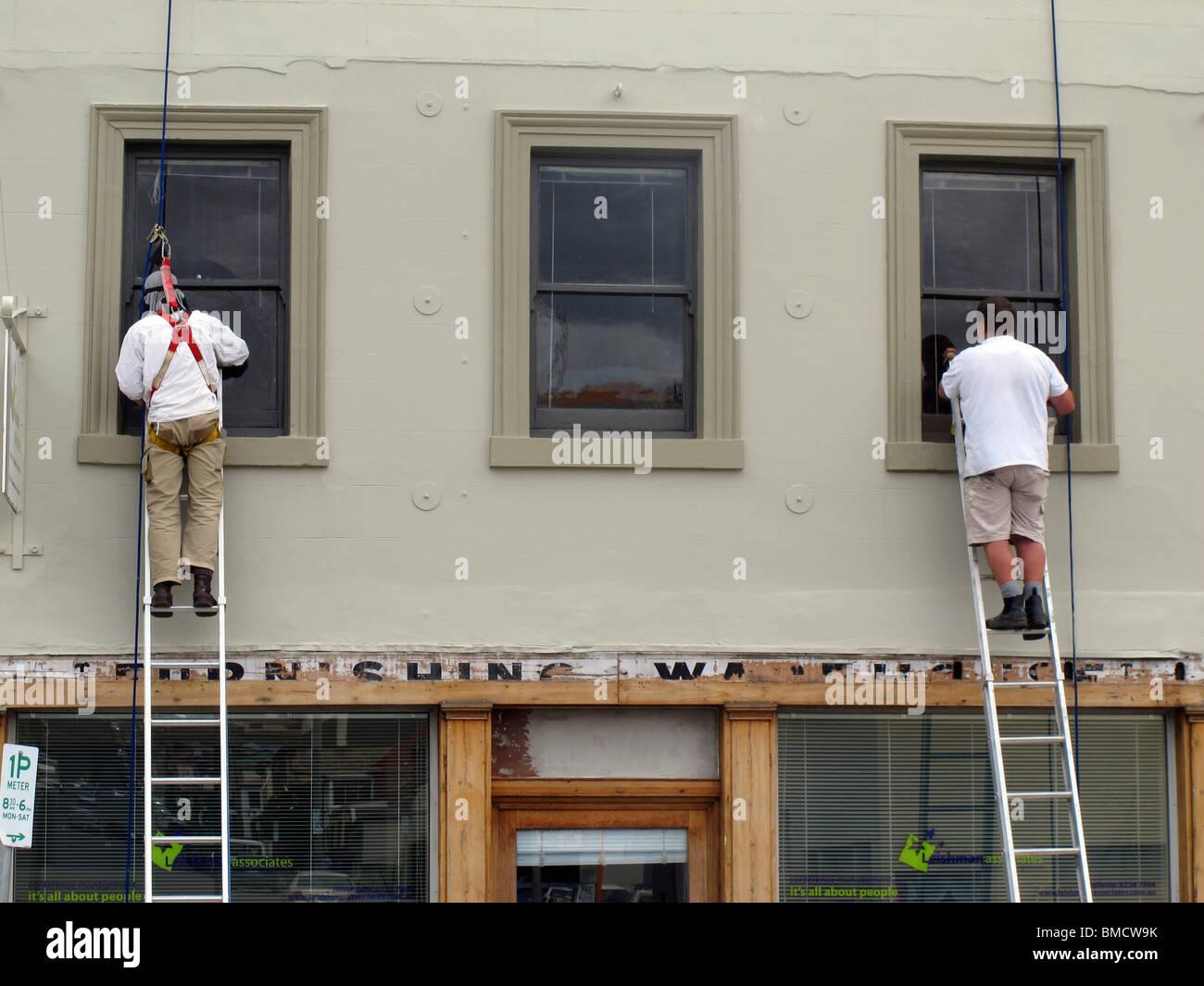 Zwei Maler auf Leitern, die Malerei der Fensterrahmen eines ...