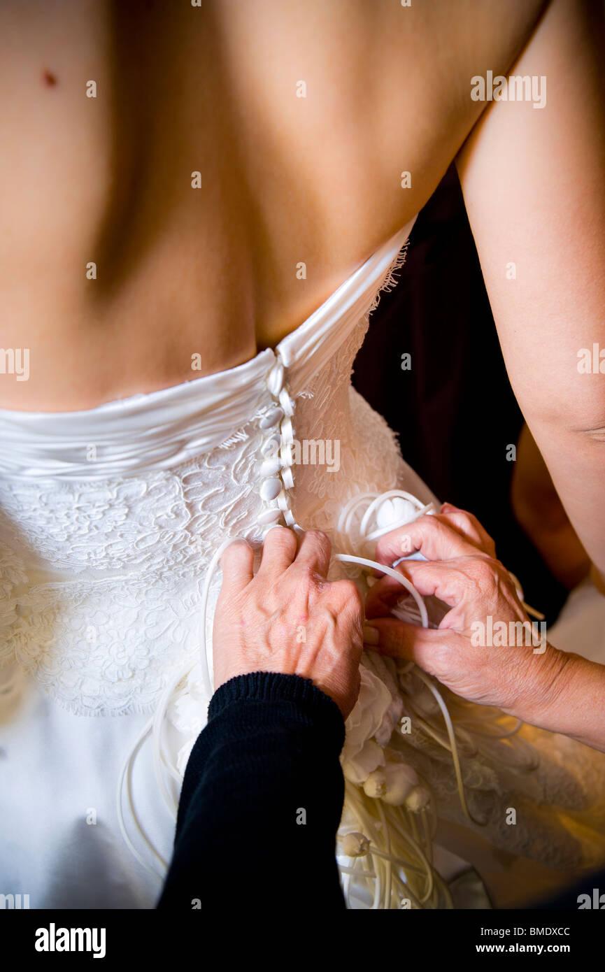 Frau knöpfte sich die Braut Brautkleid Stockbild