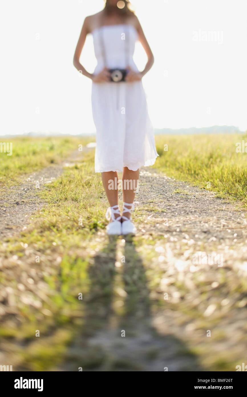 Eine Braut steht auf einer unbefestigten Straße In einem Feld mit einer Kamera um den Hals Stockbild