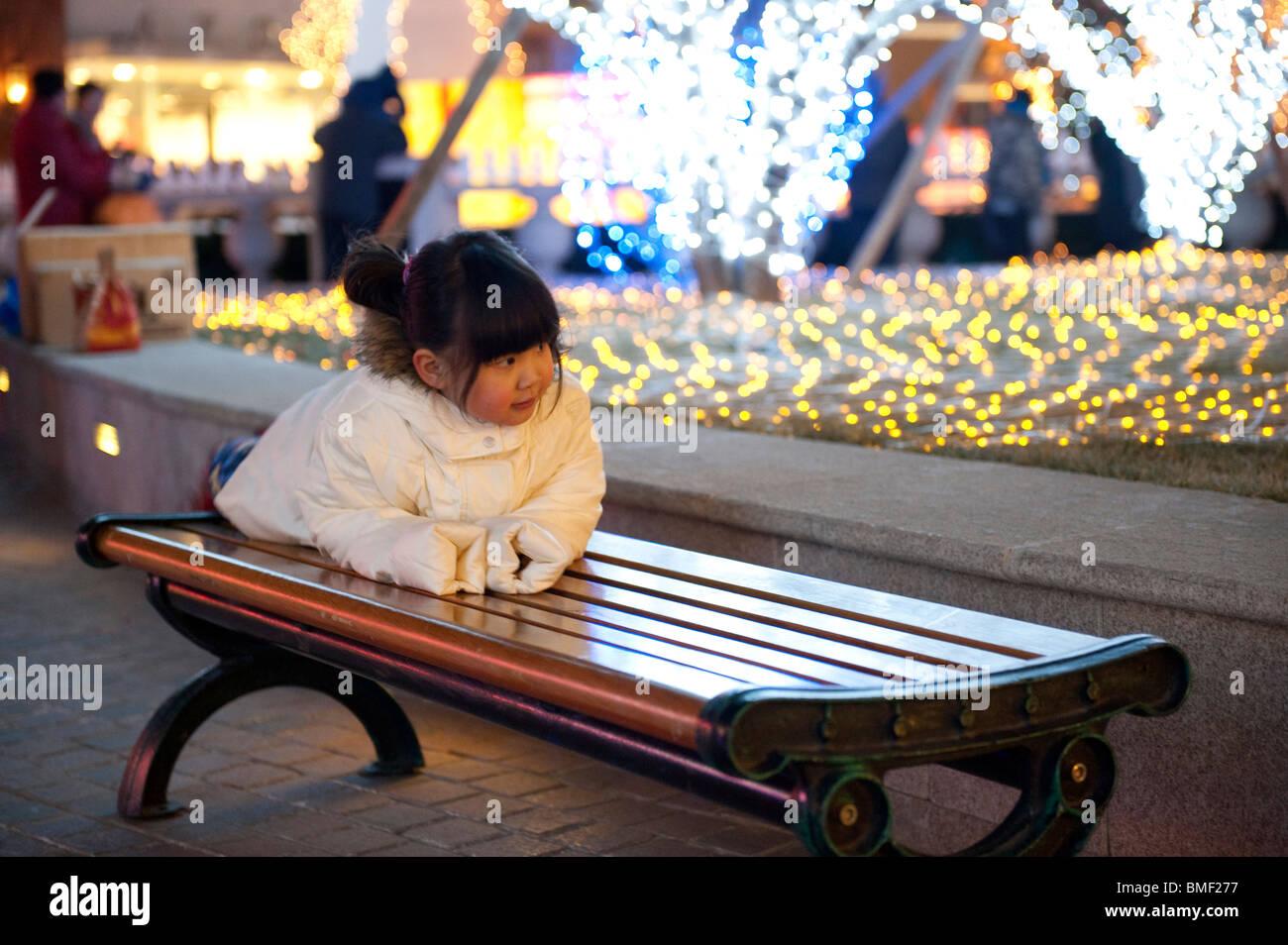 Chinesische Mädchen auf einer Parkbank Solana Lifestyle Shopping Park am Heiligabend, Peking, China Stockbild