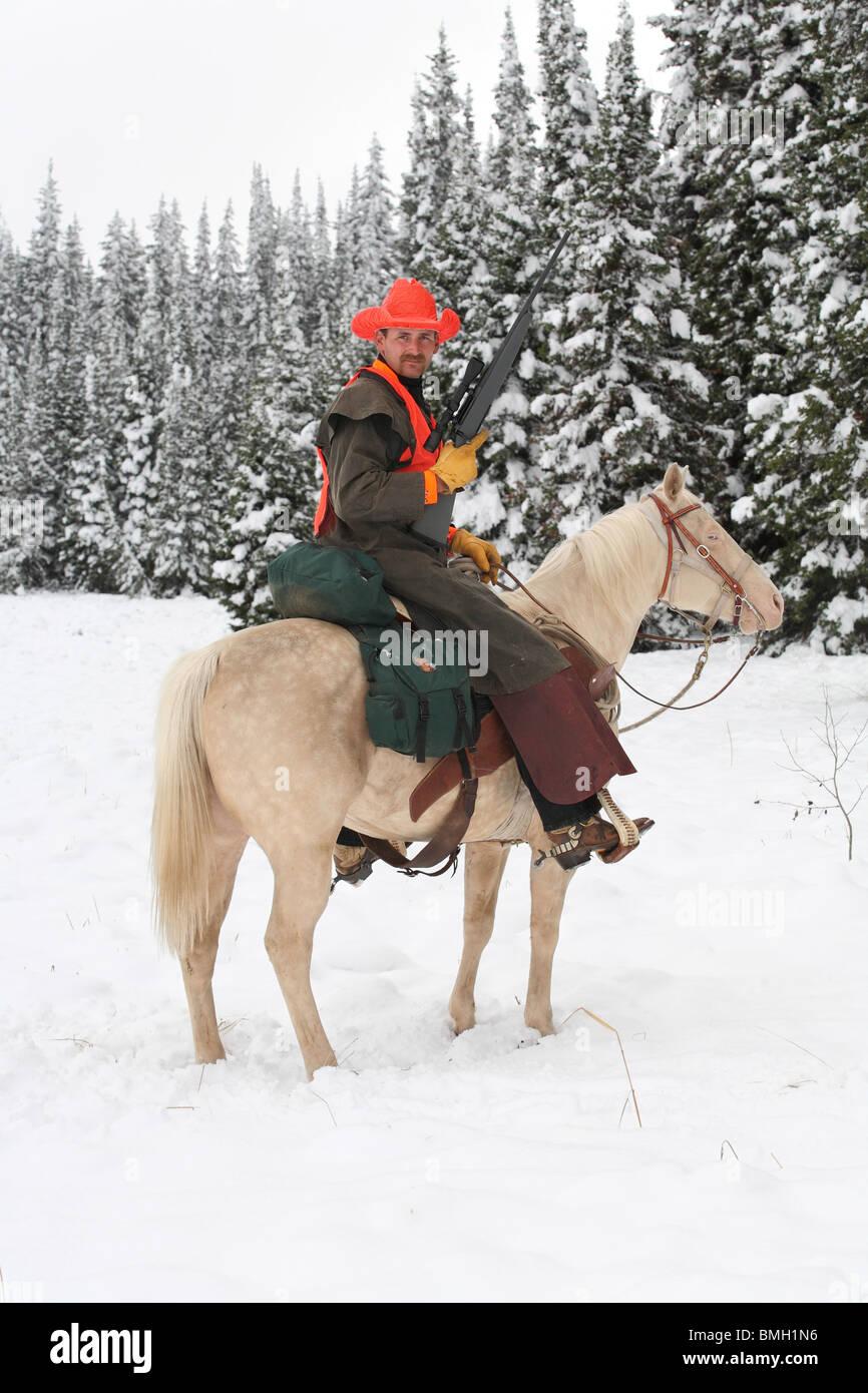 Cowboy Jäger weiß Reitpferd im Schnee mit Gewehr Jagd Stockbild
