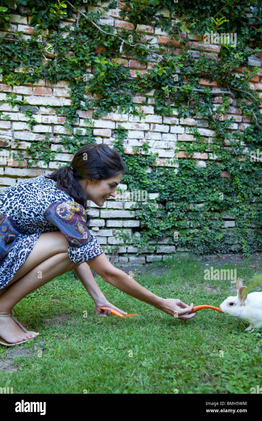 Frau, die Karotten, ein Kaninchen füttern Stockbild