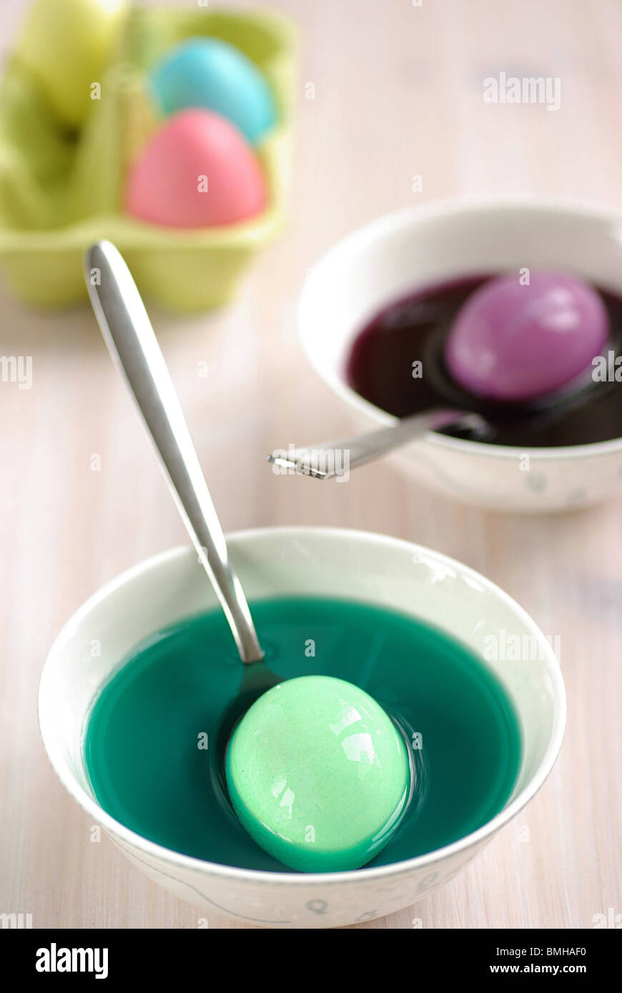 Ostereier werden in mehrere Schalen mit bunten Farbstoff gefärbt ...
