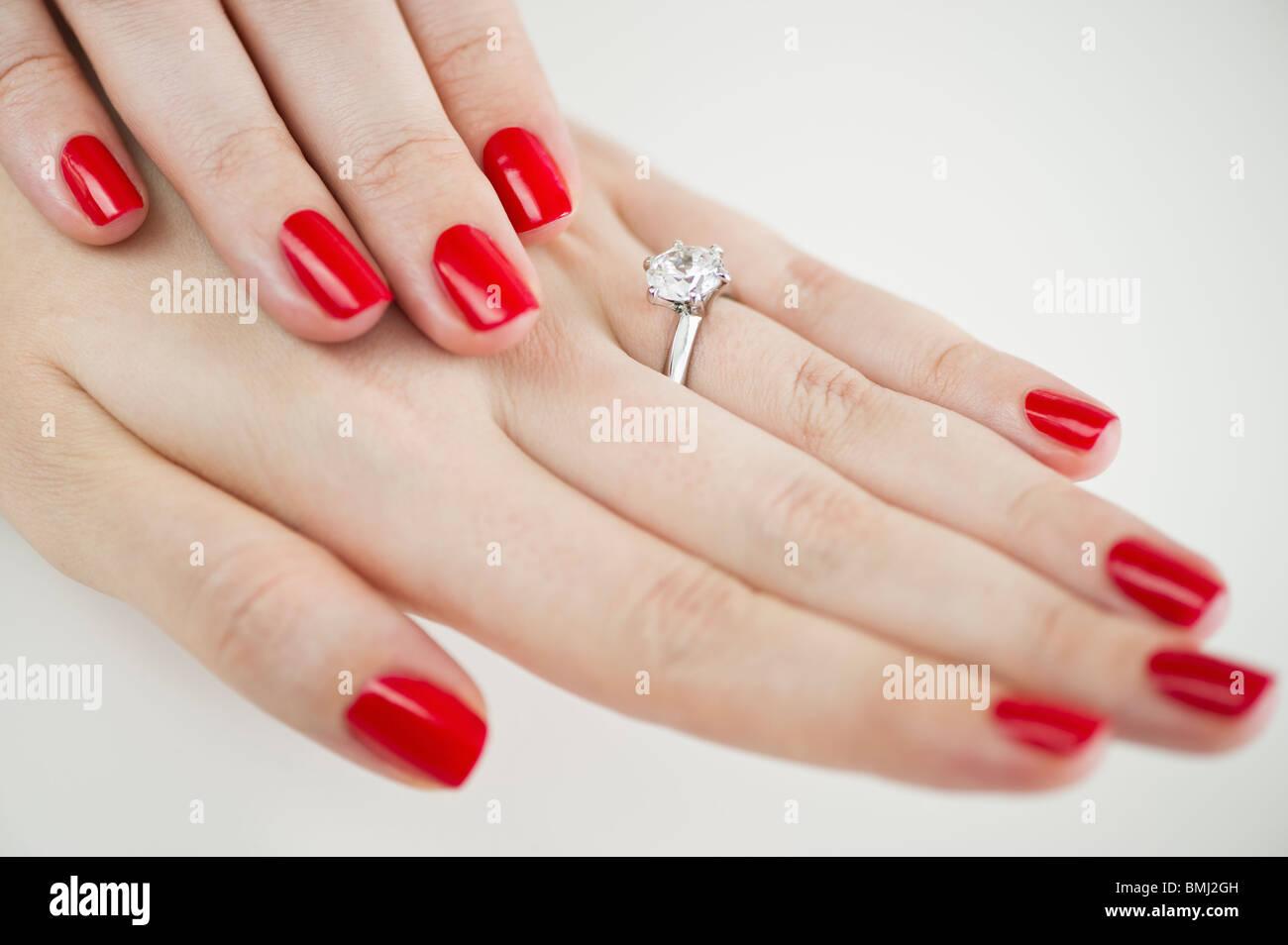Diamant-Verlobungsring auf Hände mit rotem Nagellack Stockfoto, Bild ...