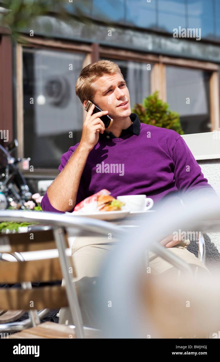 Mann sitzt auf einem Außenrestaurant am Telefon sprechen Stockbild