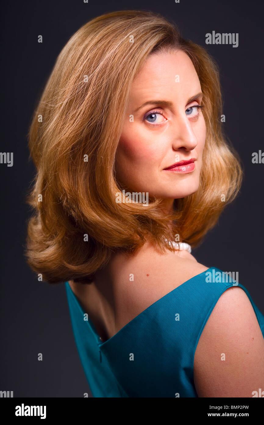 Anspruchsvolle blauäugige blonde Frau auf dunklem Hintergrund Stockbild