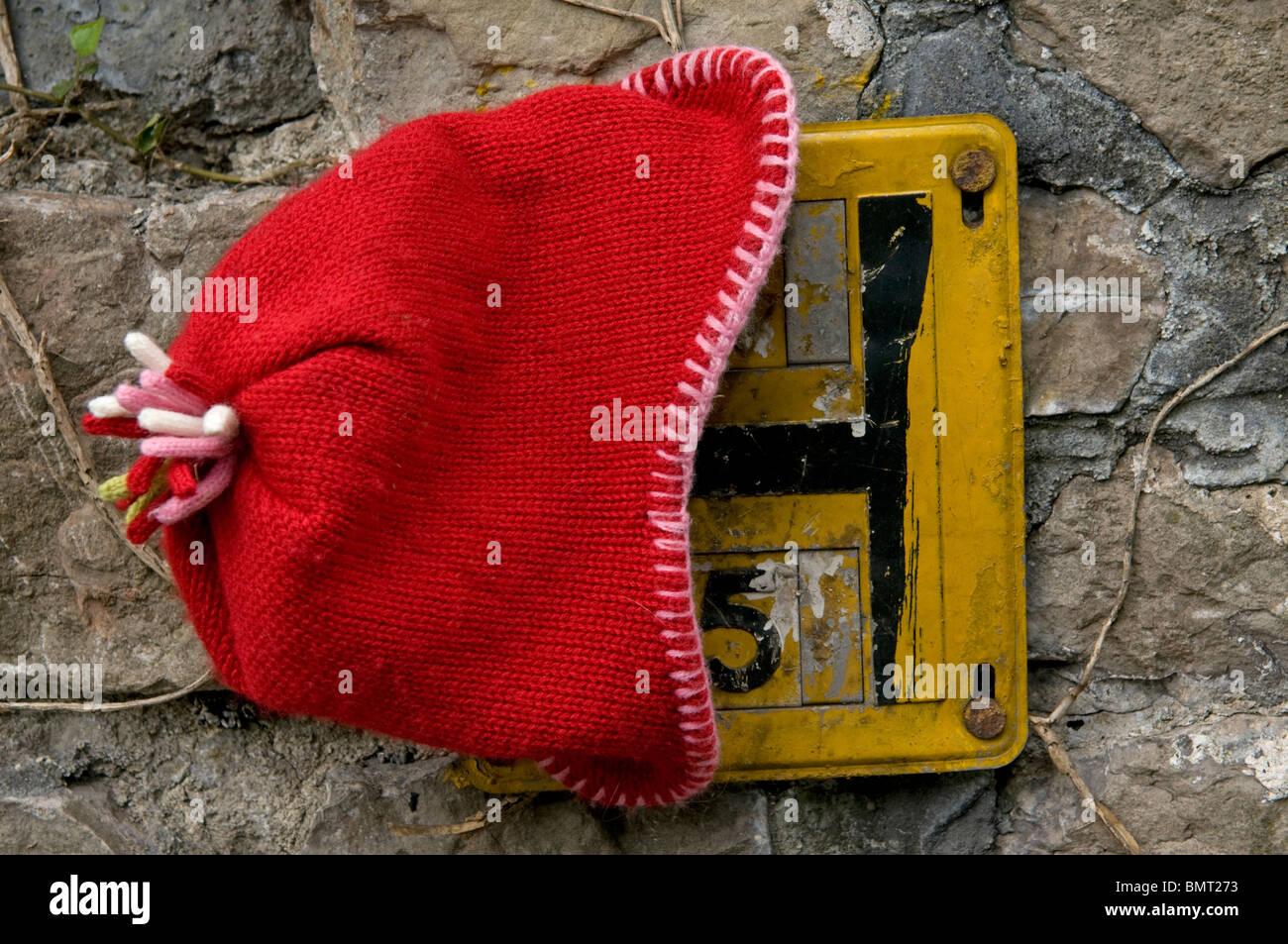 Verlorenen roten Hut platziert auf einem Hydranten-Schild Stockbild
