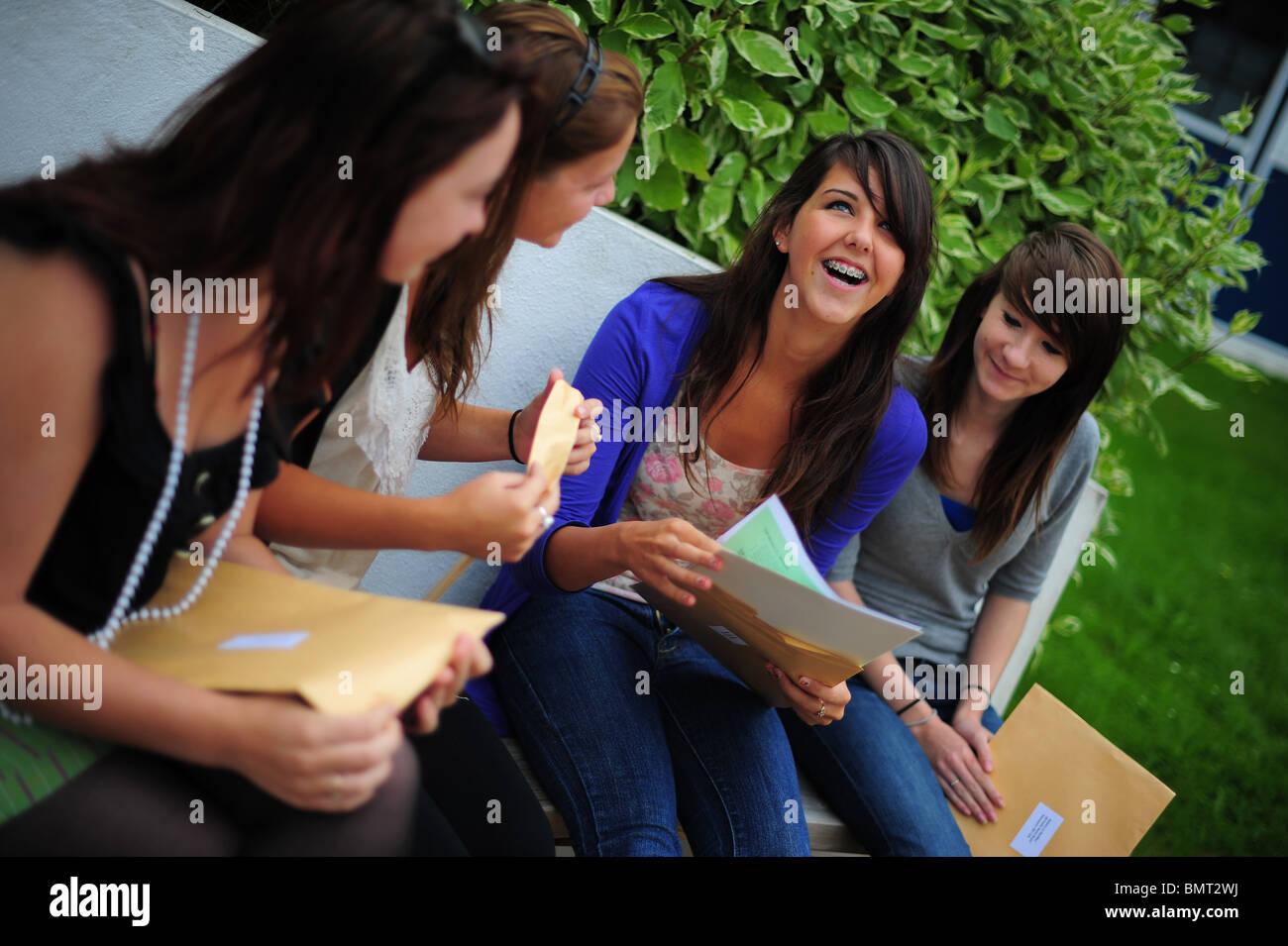 vier Schülerinnen Schüler saßen öffnen ihre GCSE-Prüfungsergebnisse in Treviglas Community Stockbild