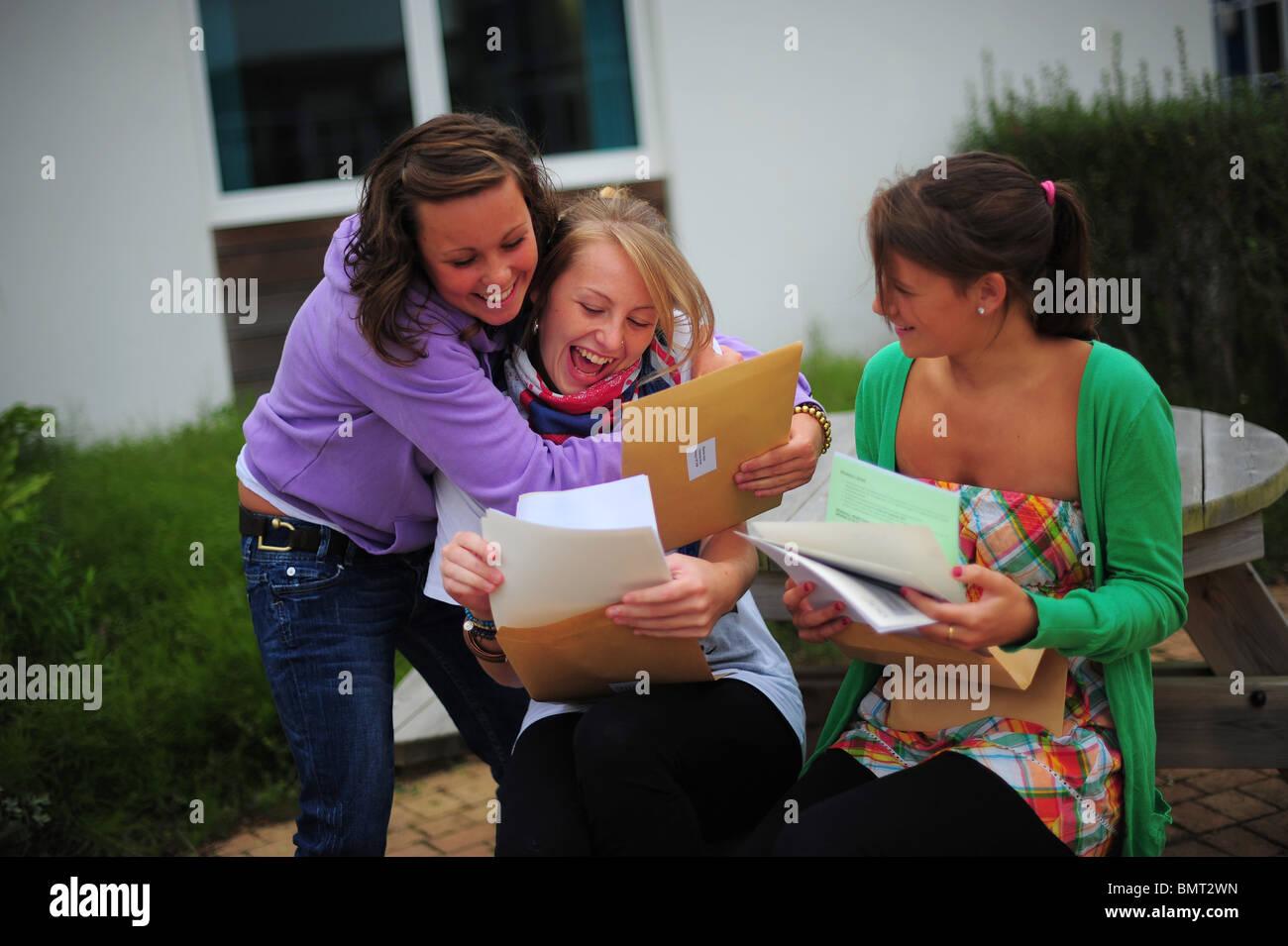 drei Mädchen der Schule-Schüler saßen öffnen ihre GCSE-Prüfungsergebnisse in Treviglas Stockbild