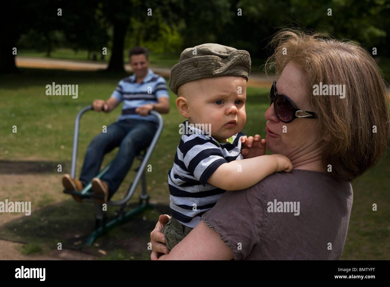 Ein elf Monate altes Kleinkind hielt sich fest um seine 40-etwas Tante als Papa Übungen hinter. Stockfoto