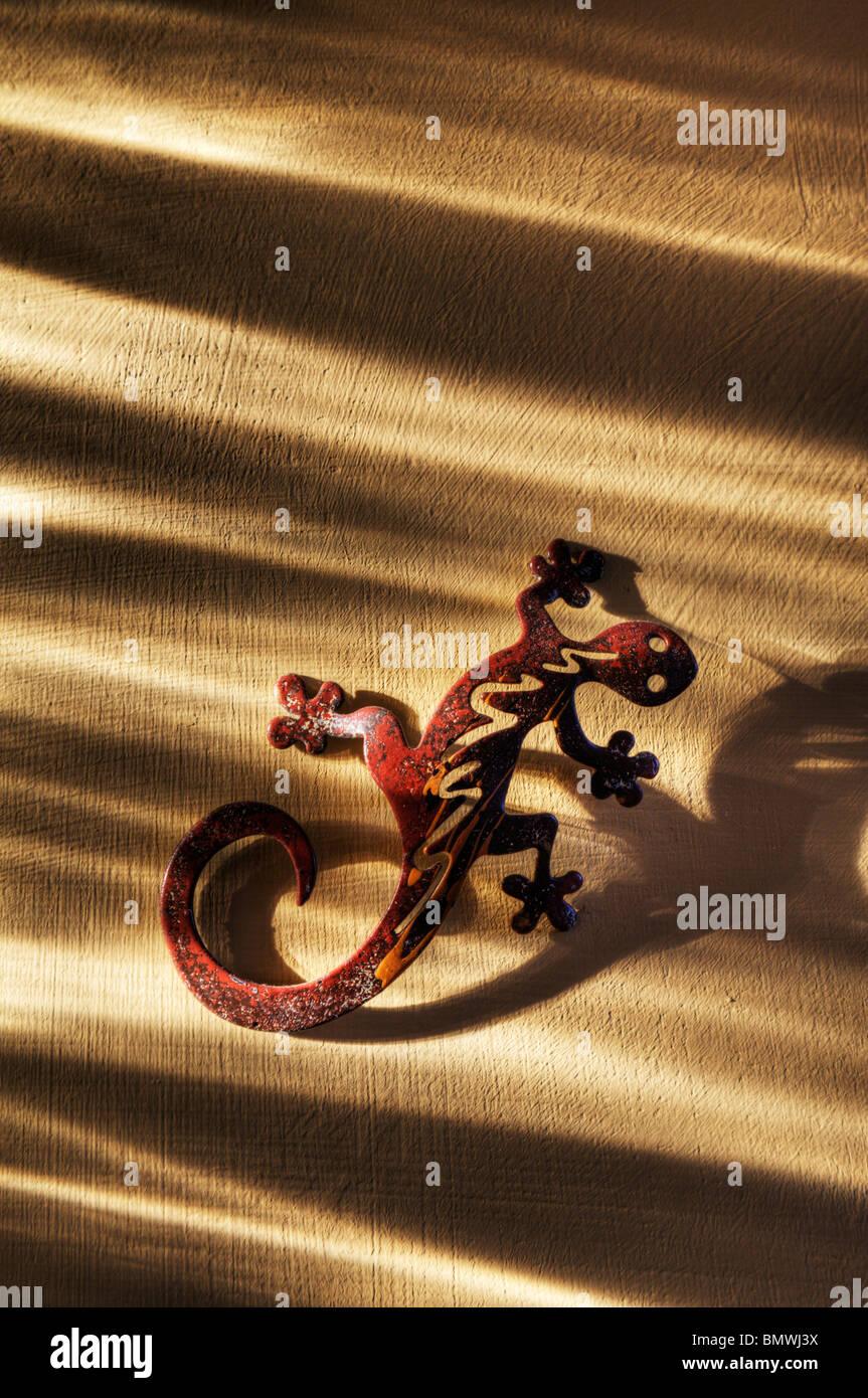 Ein symbolischer Gecko an der Wand. Stockbild