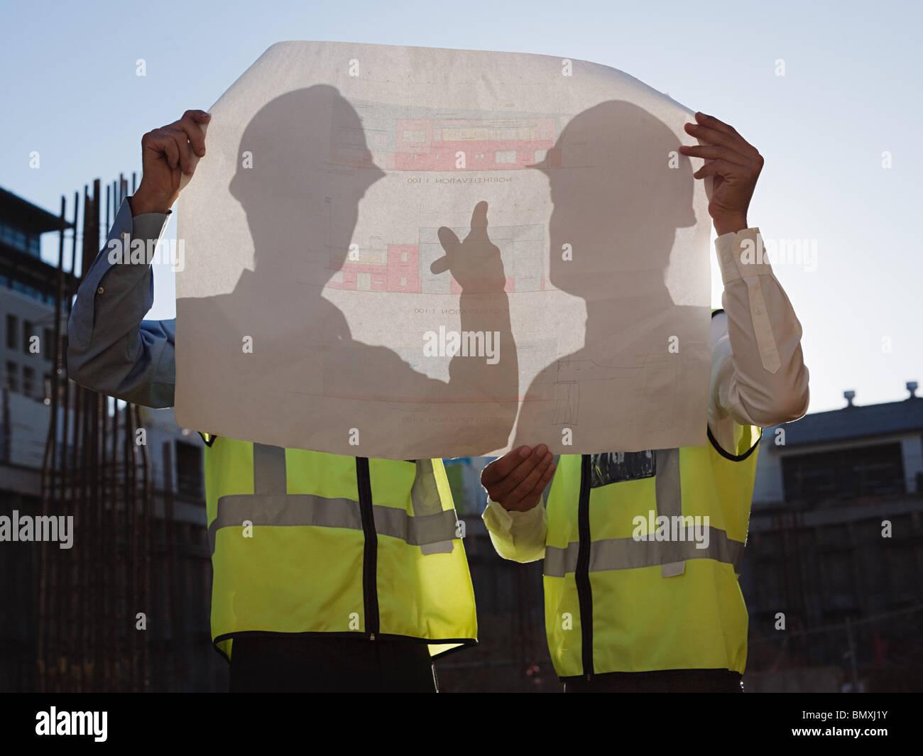 Reife Männer mit Blaupause auf Baustelle Stockbild