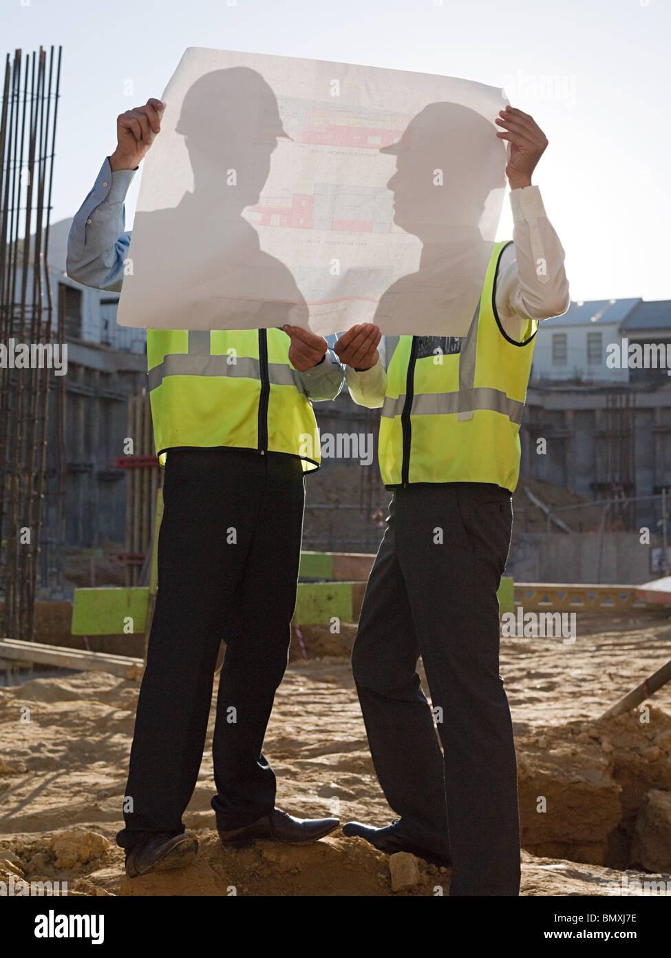 Reife Männer Inspektion Blaupausen auf Baustelle Stockbild