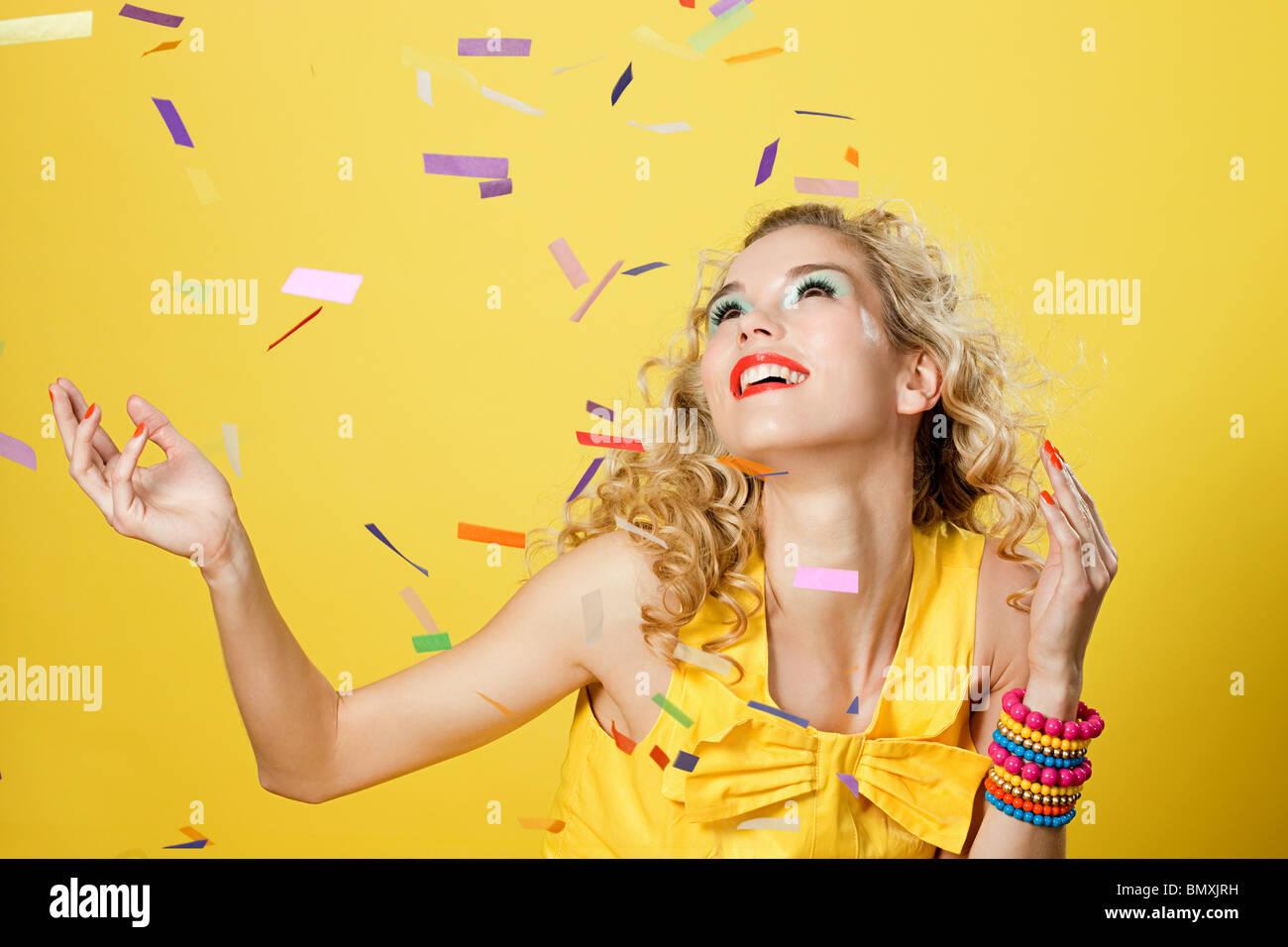 Junge blonde Frau mit bunten Konfetti Stockbild