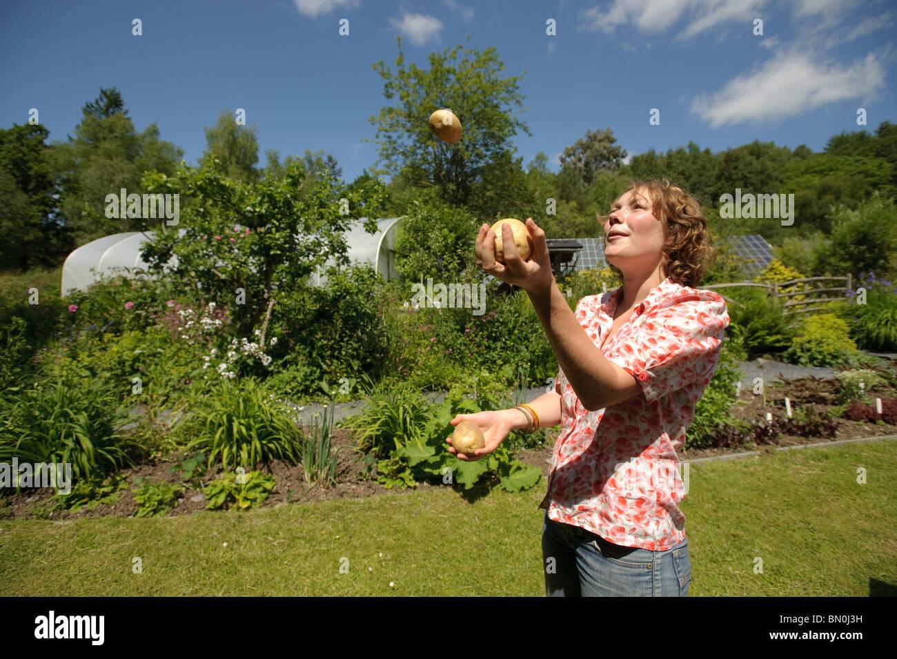 Eine Frau, Jonglieren mit drei Kartoffeln in der Mitte für Alternative Technologie, Machynlleth, Powys Wales Stockbild
