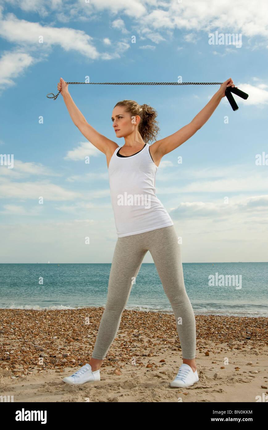 Frau am Strand dehnen Stockbild