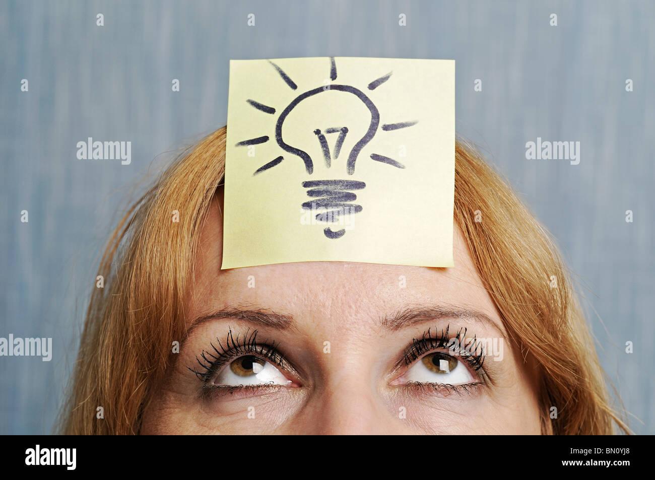 Ideen, Frau mit einer Zeichnung von einer Glühbirne auf dem Kopf. Stockbild