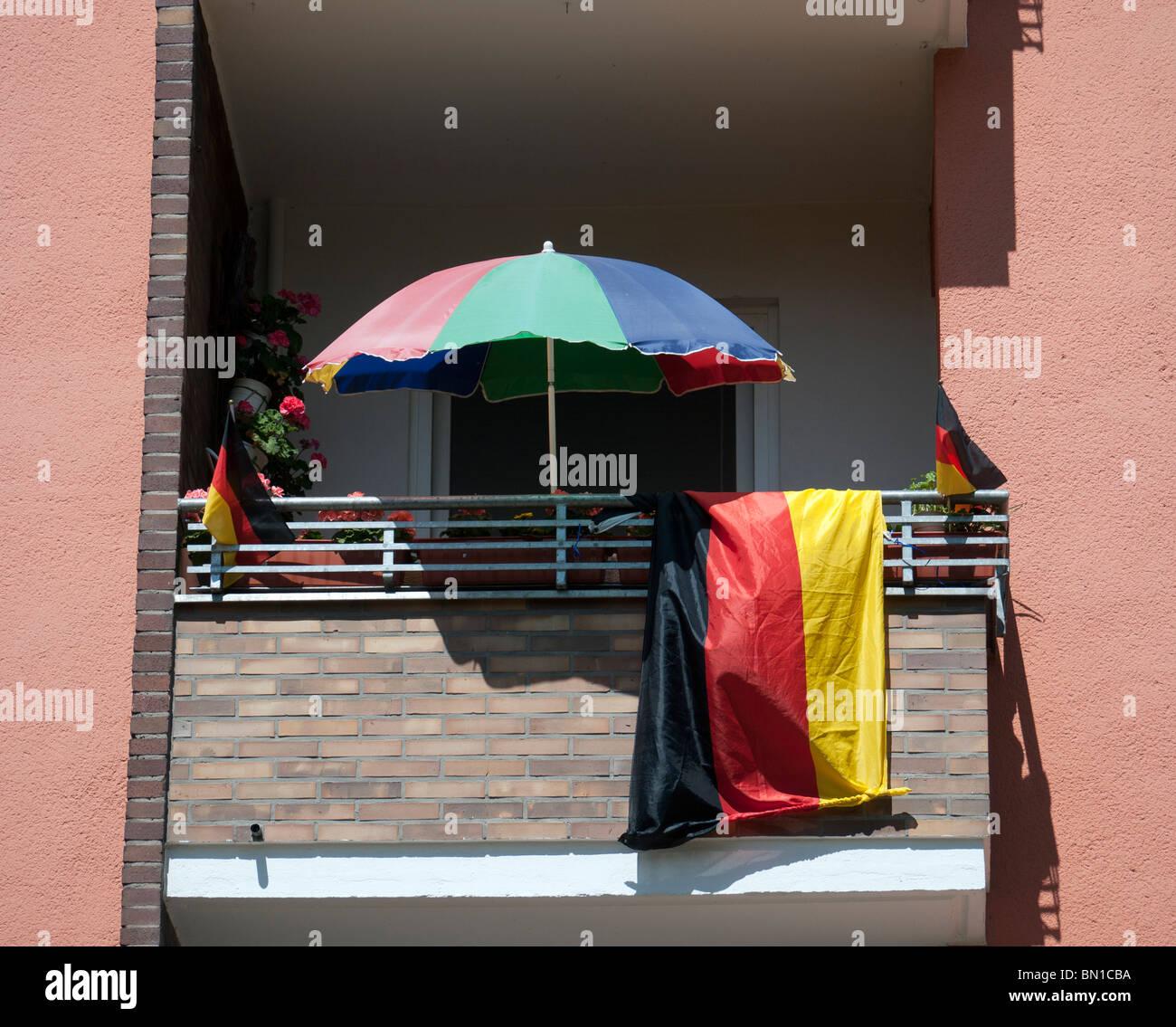 Balkon mit deutscher Flagge und Sonnenschirm während der Fußball WM 2010 in Berlin Deutschland Stockbild