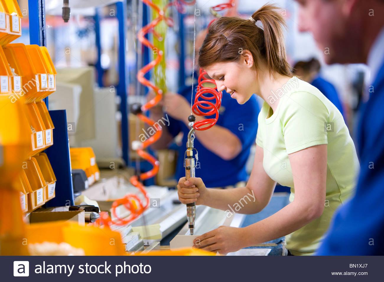 Arbeiter, die Bedienung von Maschinen auf Produktionslinie im Werk, das Aluminium Leuchten herstellt Stockbild