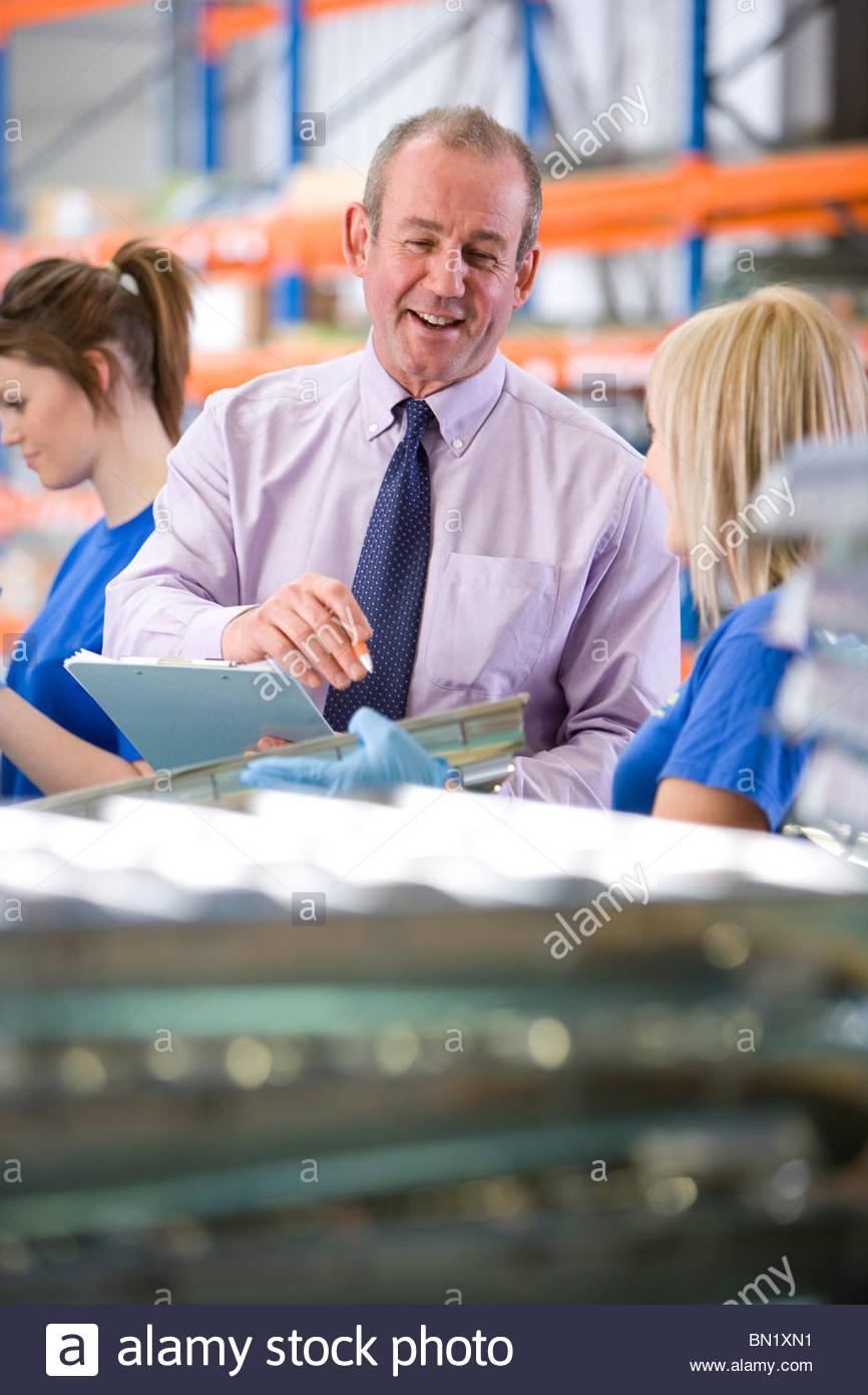 Manager, die Inspektion Alu leichte Montage durch Arbeiter in Fabrik gehalten Stockbild