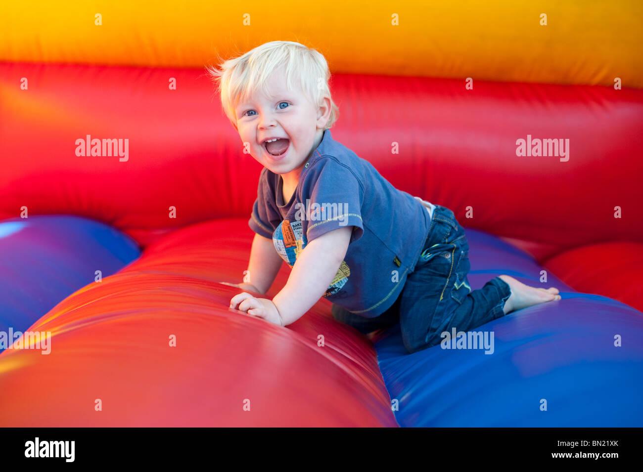 Bot-Kleinkind mit blonden Haaren auf der Hüpfburg spielen Stockbild