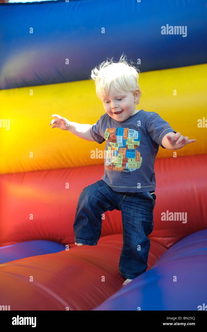 Kleinkind Schritten aufgeregt auf Hüpfburg Stockbild