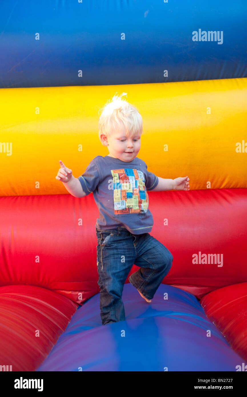 Junge Kleinkind vorläufig zu Fuß auf der Hüpfburg Stockbild