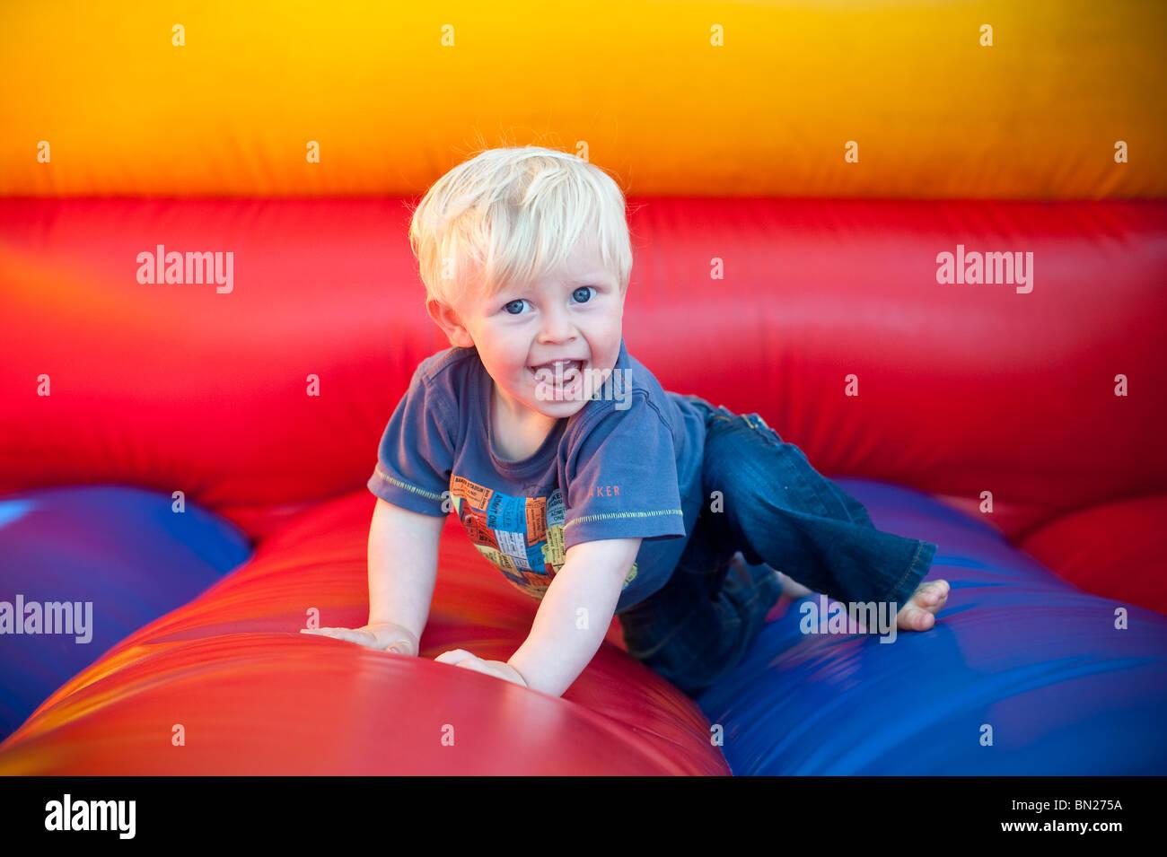 Glücklich lächelnd blonde junge Kleinkind auf der Hüpfburg spielen Stockbild