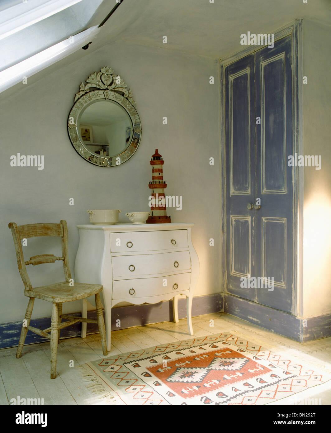Teppich am Boden vor Holzstuhl und weiße Kommode im Schlafzimmer ...