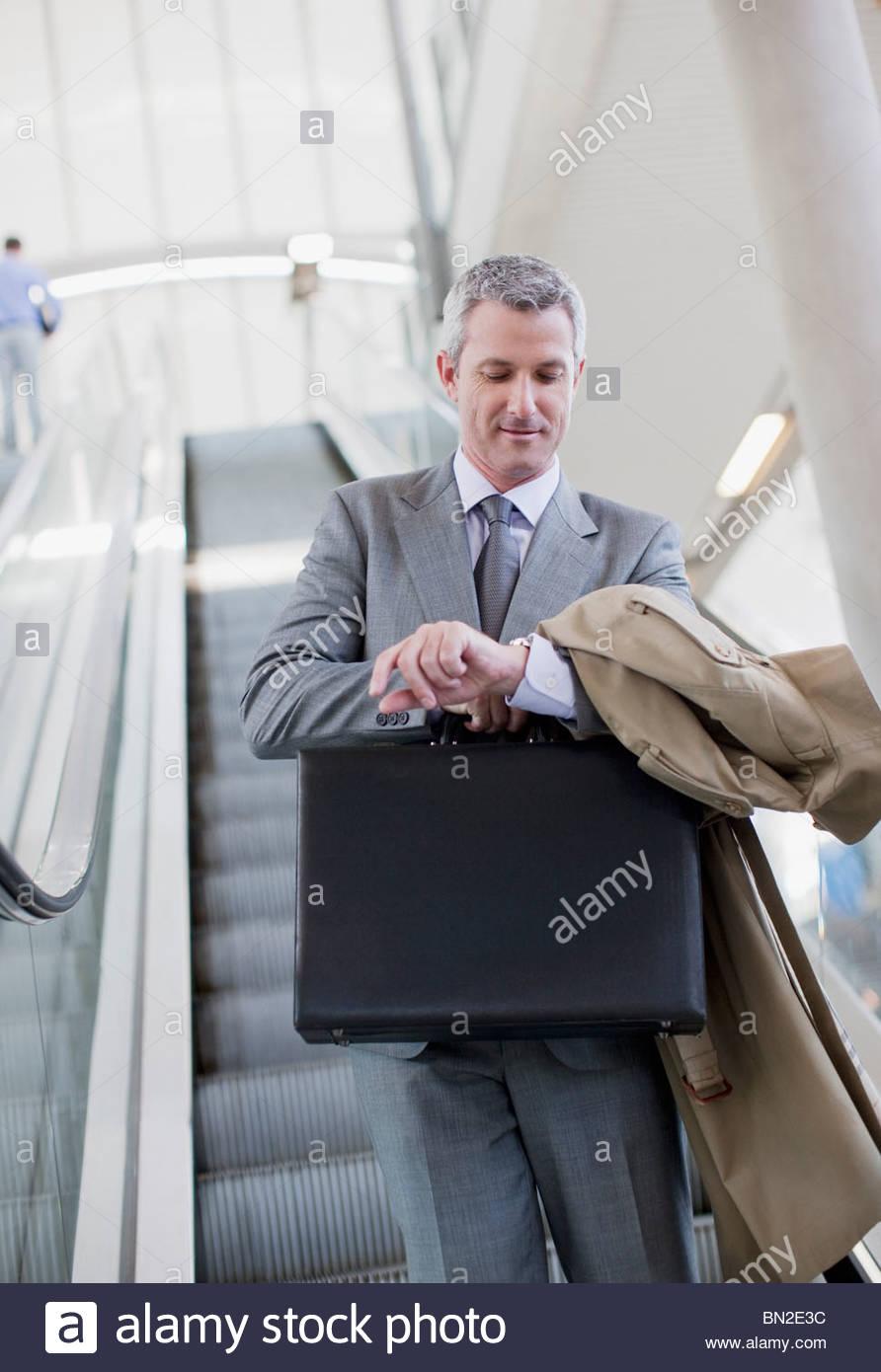 Geschäftsmann absteigend Rolltreppe und überprüfen der Zeit Stockbild