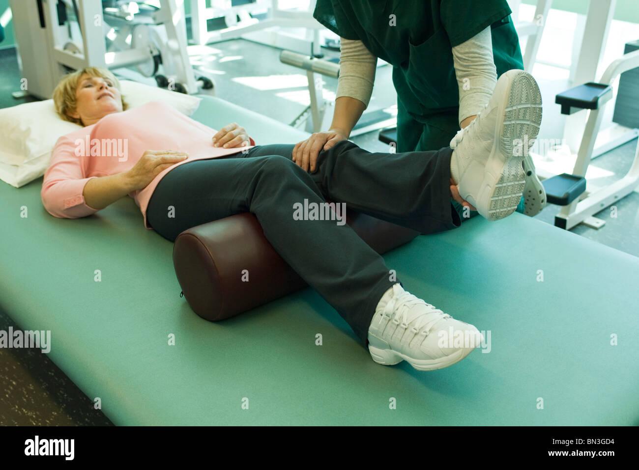 Frau von Physiotherapeuten behandelt zu werden Stockbild