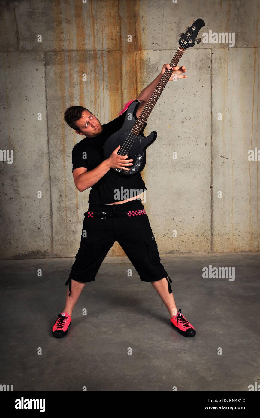 Man spielt Bassgitarre in industriellen Grunge-Umgebung Stockbild