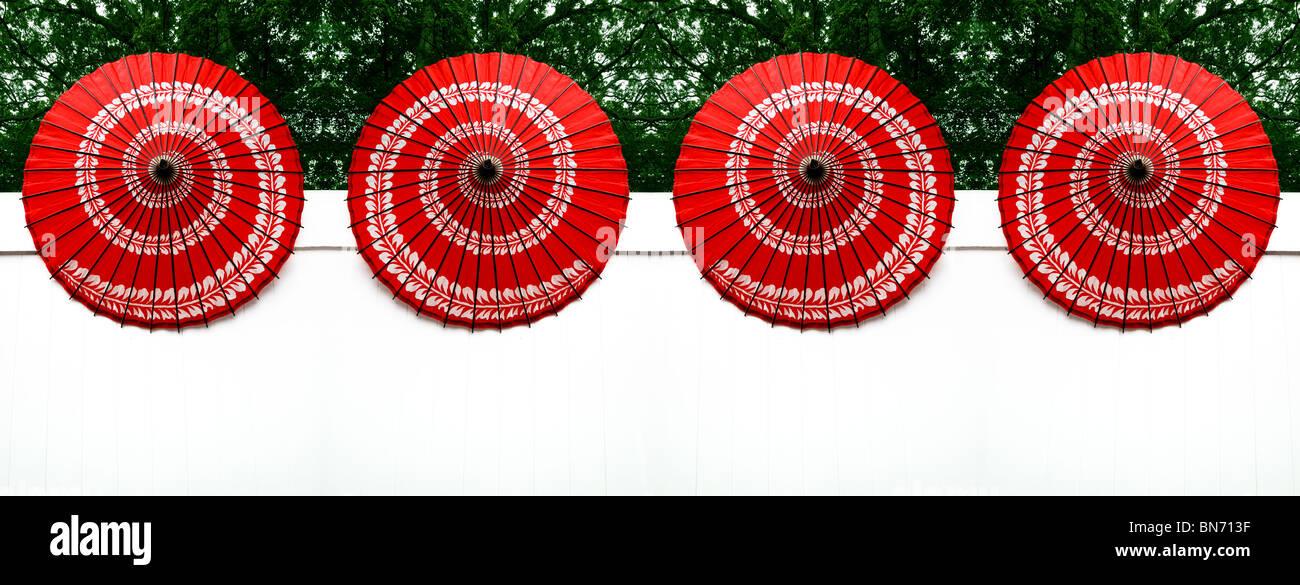 Vier helle rote chinesische Papier Sonnenschirme mit einem wirbelte Muster sitzen in einer Reihe auf einem weißen Stockbild