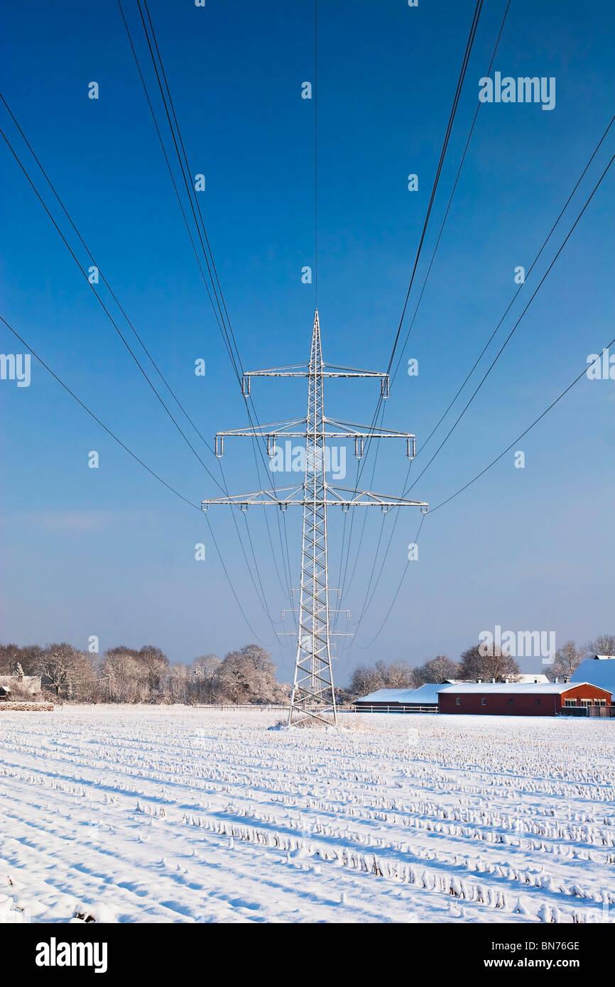 Stromleitung mit Schnee und blauer Himmel Stockbild