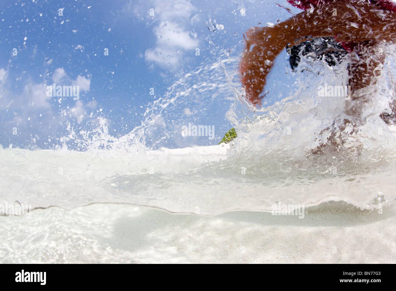 Spielen im flachen Wasser, auf einem abgelegenen Atoll in den Malediven-Kette, Indischer Ozean Stockbild