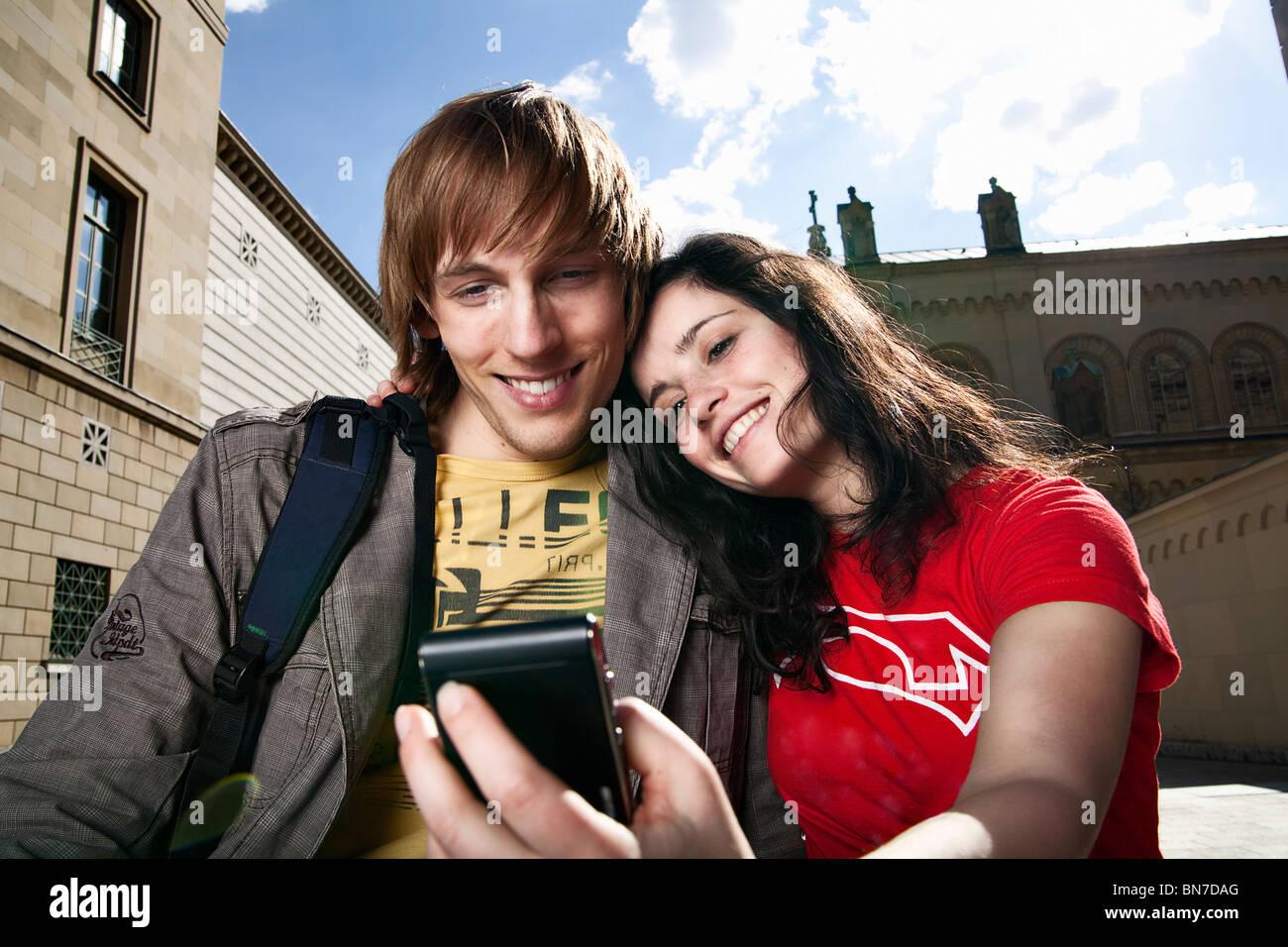 Junge Touristen, die gerne am Handy Stockbild