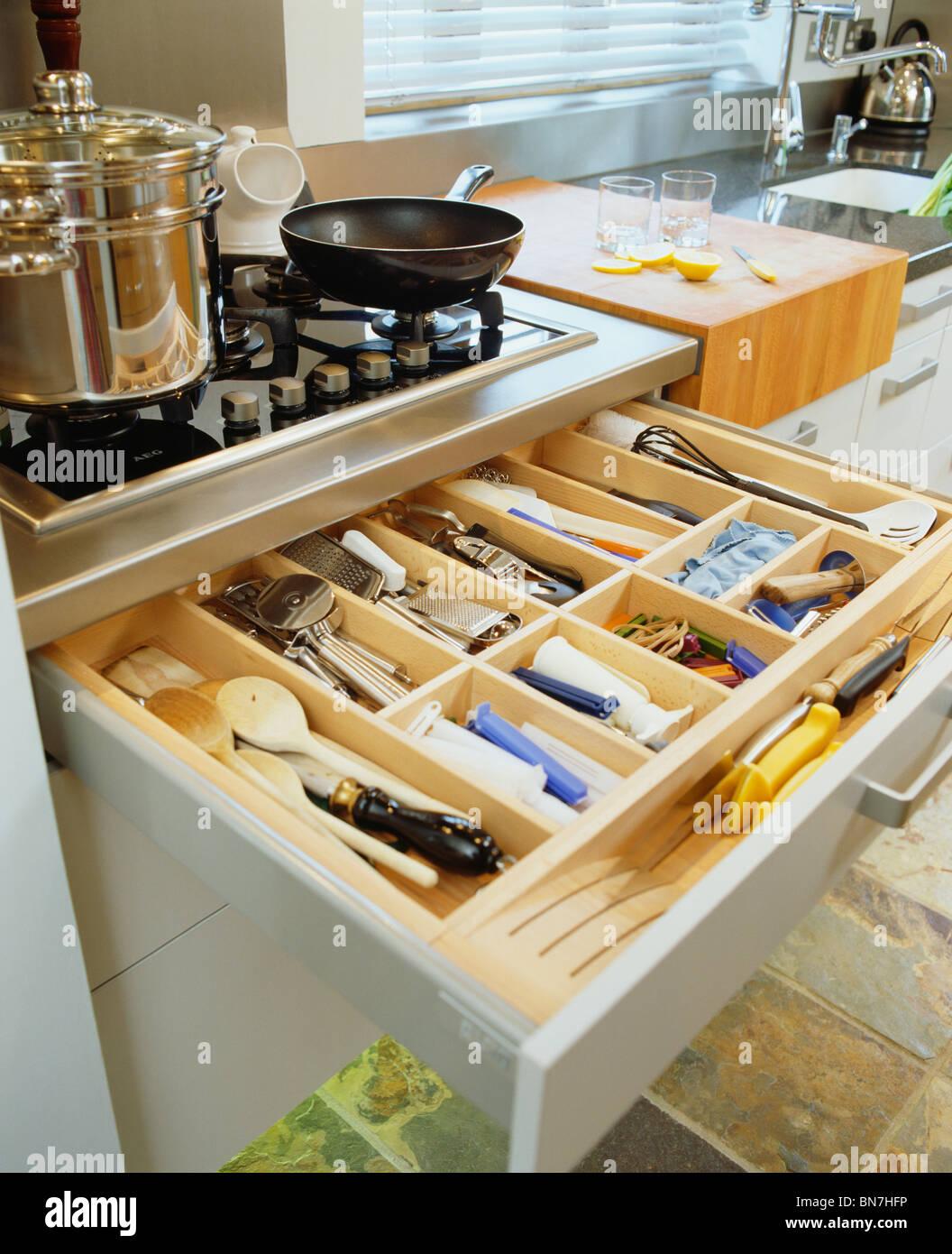 nahaufnahme des offenen besteckschublade unter pfannen auf. Black Bedroom Furniture Sets. Home Design Ideas