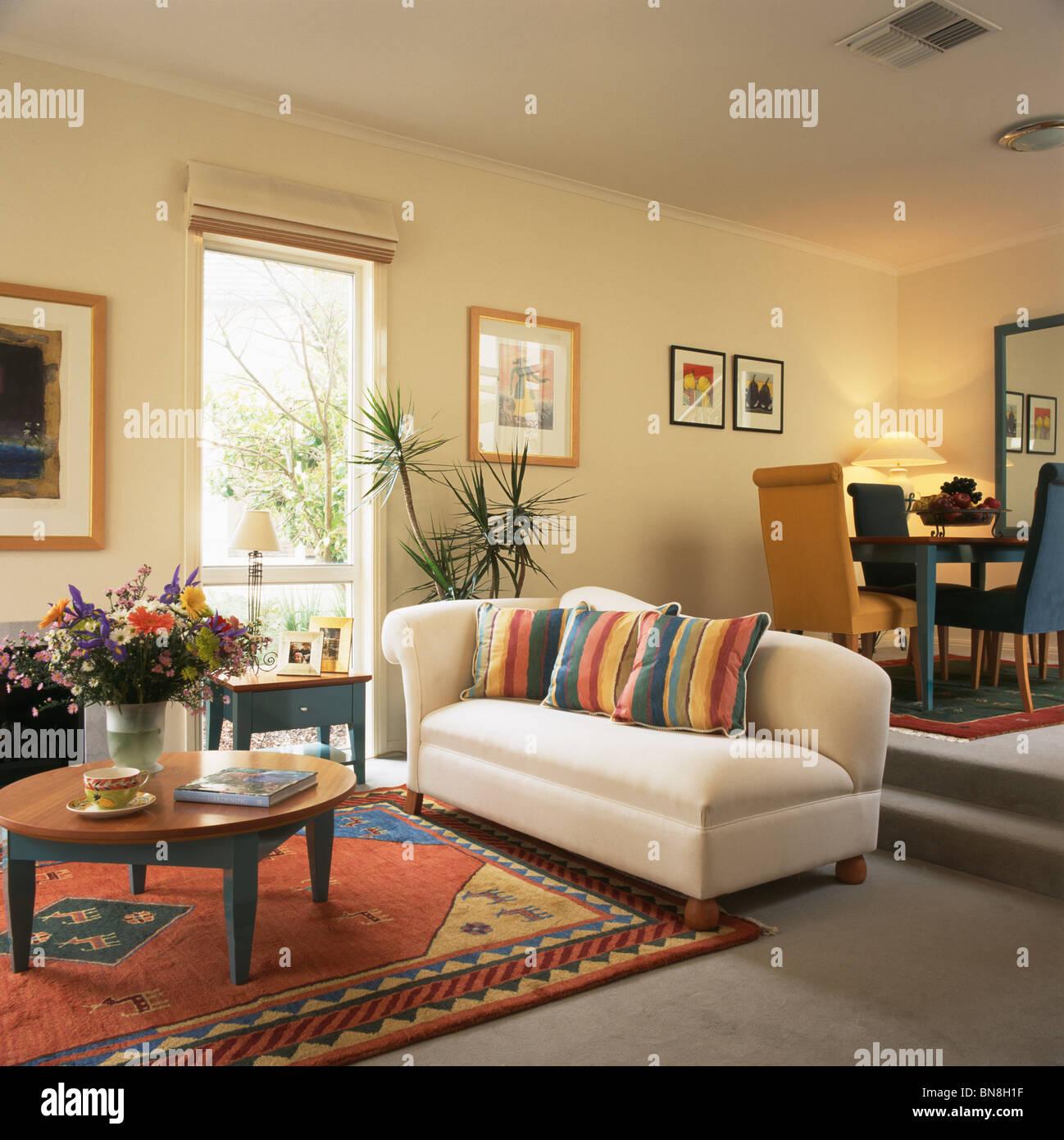 Bunt Gestreifte Kissen Auf Weißen Sofa Und Bunt Gemusterten Teppich Am  Boden In Moderner Split Level Wohnzimmer Und Esszimmer