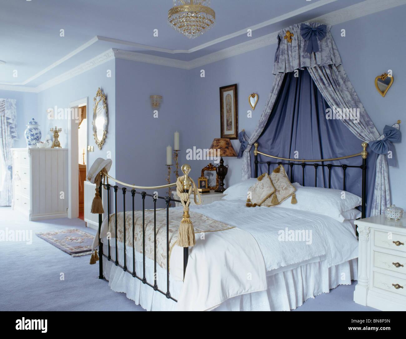 Coronet mit blauen Vorhängen über Messingbett mit weißen Bettwäsche ...