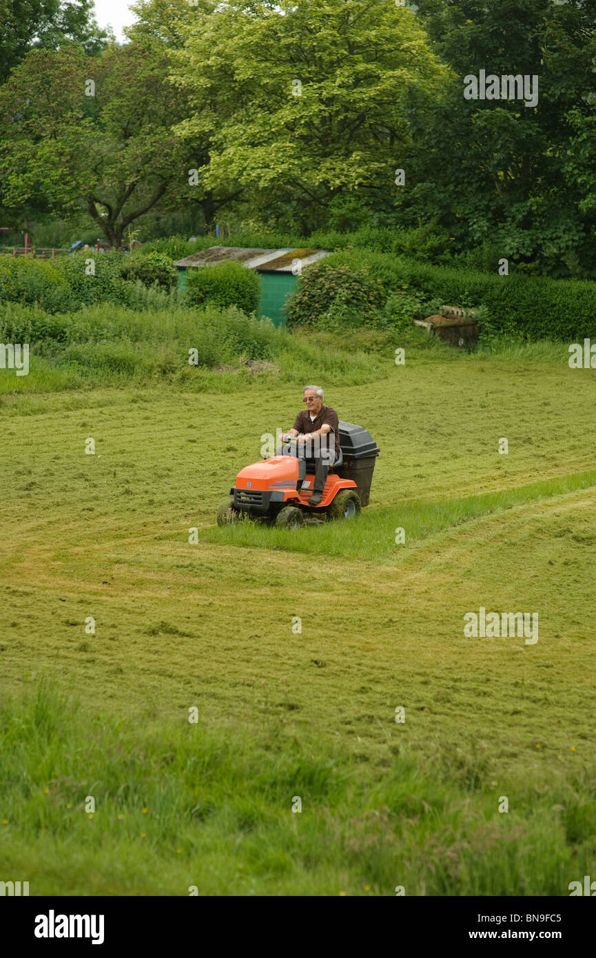 ein Mann mit einem Sit-on-Rasenmäher mähen, uk Stockbild