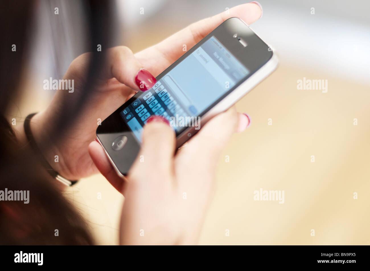 Mädchen-SMS auf Apple Telefon I 4 smart Phone-Close-up Stockbild