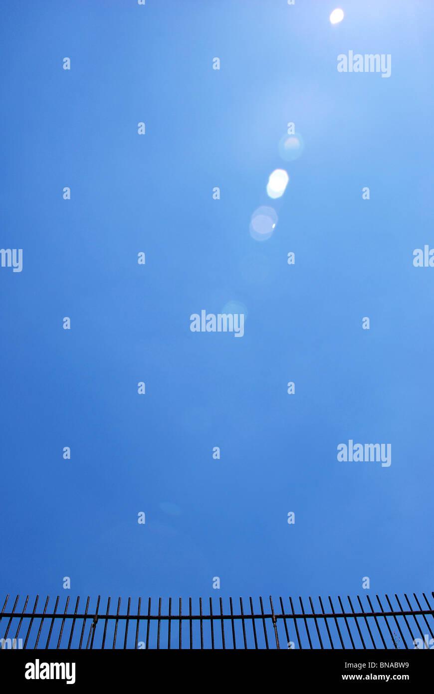 Schmiedeeisernen Zaun vor einem wolkenlosen, blauen Himmel mit Blendenfleck Stockbild