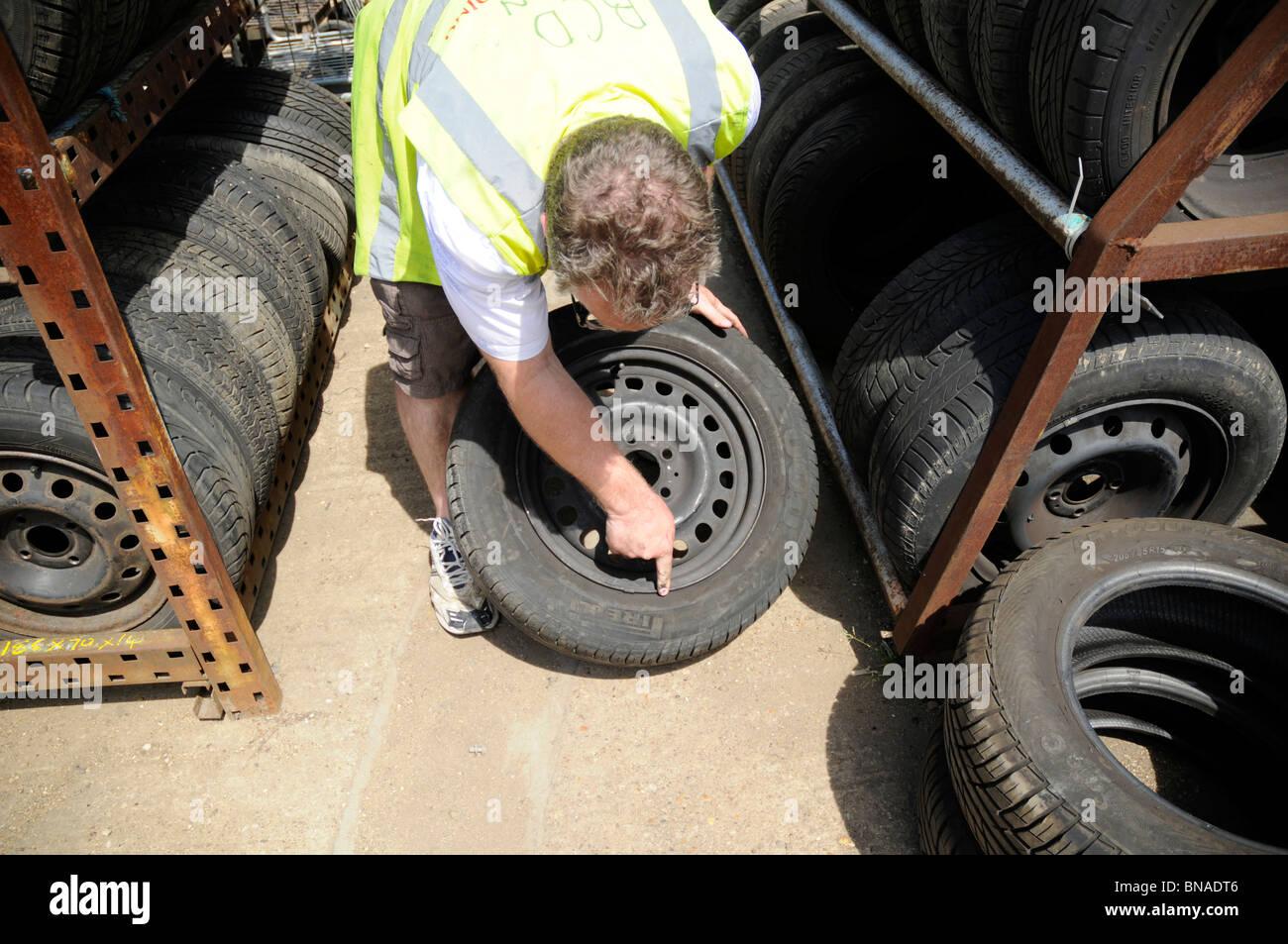 Mann mit hi-Vis Weste Inspektion von Rad und Reifen in einem Auto Breakers Yard. Stockfoto