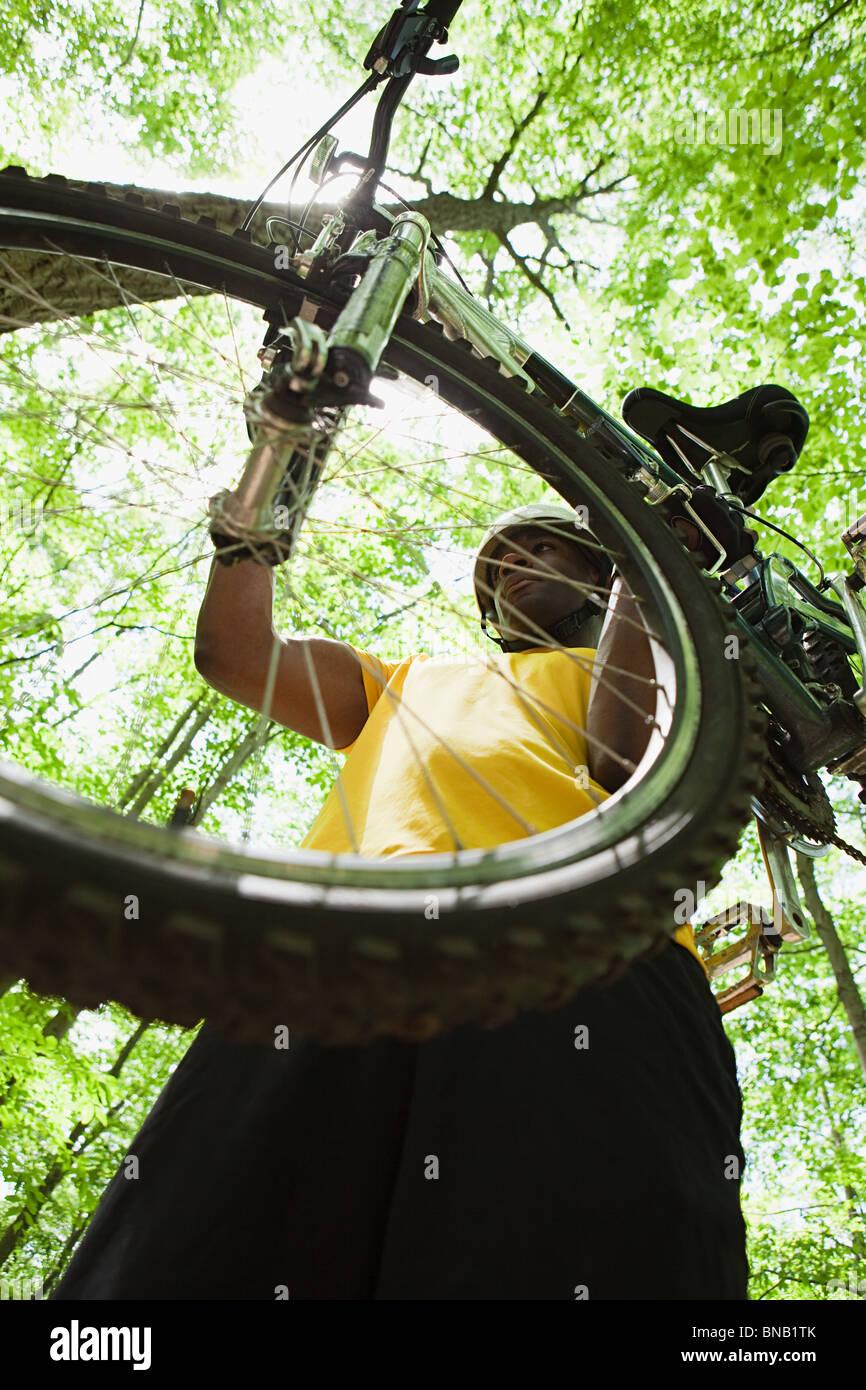 Männliche Radfahrer tragen Fahrrad im Wald Stockbild
