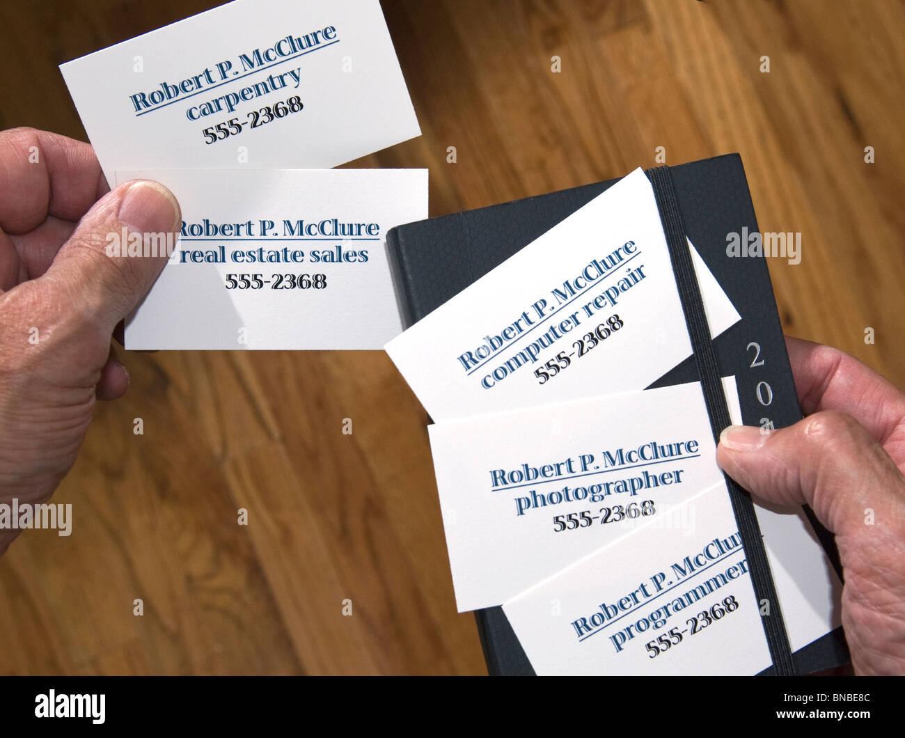 Nahaufnahme der Hände halten mehrere Visitenkarten mit unterschiedlichen berufen Stockbild